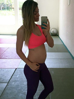 Pregnant young girl in a swimsuit gym..